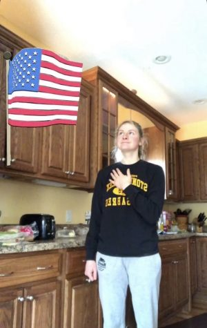 Mary Kromer stands for the Pledge to the Flag...in her kitchen.